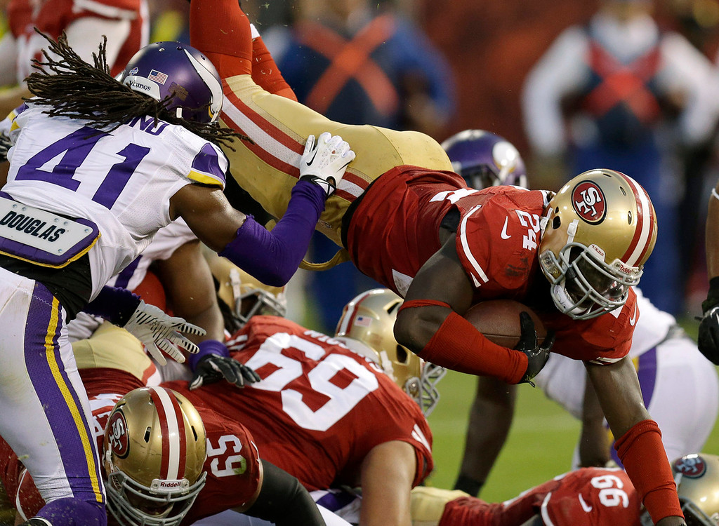 . 49ers running back Anthony Dixon dives into the end zone past Vikings defensive back Mistral Raymond, left, to score on a one-yard touchdown run during the fourth quarter. (AP Photo/Ben Margot)