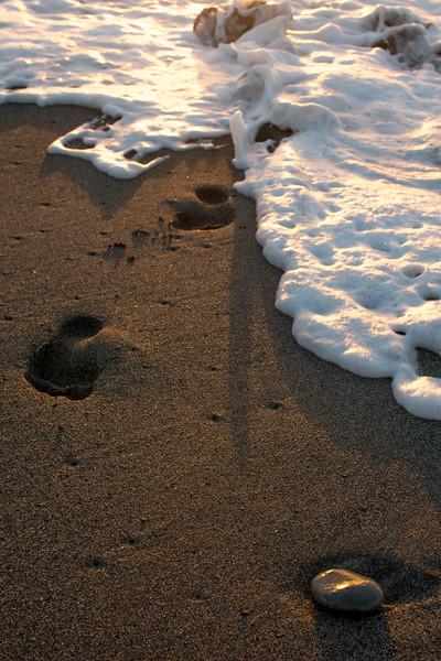 foam washing over foot prints and stone-1.jpg