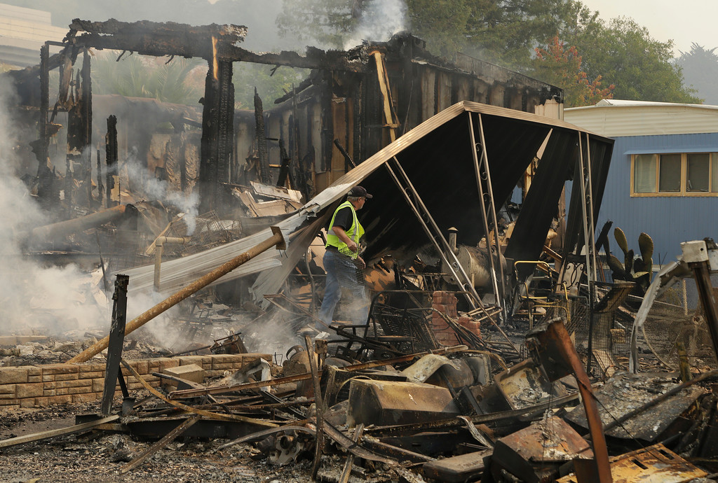 . Jim Cook, manager of the Journey\'s End mobile home park, walks through what remains of his home on Monday, Oct. 9, 2017, in Santa Rosa, Calif. Wildfires whipped by powerful winds swept through Northern California, sending residents on a headlong flight to safety through smoke and flames as homes burned. (AP Photo/Ben Margot)