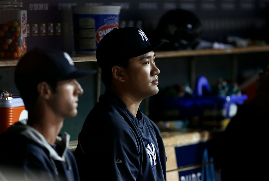 . New York Yankees pitcher Masahiro Tanaka watches against the Detroit Tigers from the dugout in the second inning of a baseball game in Detroit Tuesday, Aug. 26, 2014. (AP Photo/Paul Sancya)