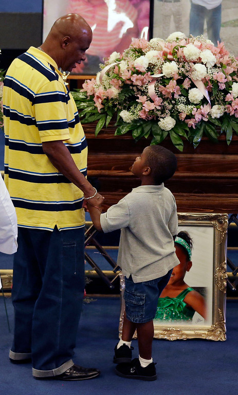 . A man and child pause at the casket during funeral services for 6-year-old Ahlittia North in Gonzales, La., Monday, July 22, 2013. Ahlittia was stabbed to death after disappearing from her mother\'s suburban New Orleans apartment more than a week ago. Her body was found days later. (AP Photo/Gerald Herbert)