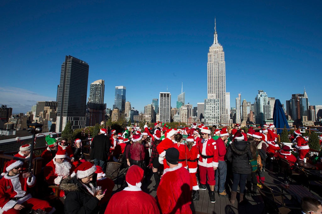 . Revelers dressed in holiday theme costumes participate in SantaCon on a rooftop bar, Saturday, Dec. 13, 2014, in New York.  SantaCon organizers retained lawyer Norman Siegel  last week as part of an effort to tame the excesses of the daylong party.  Siegel said the government cannot ban SantaCon. But he said the government can reasonably regulate the event. (AP Photo/John Minchillo)