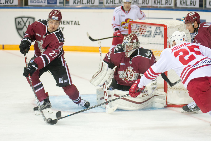 Defence man of Dinamo Riga Oskars Cibulskis (27) kicks the puck from the front of the goal  in the KHL regular championship game between Dinamo Riga and Jokerit, played on September 13, 2016 in Arena Riga