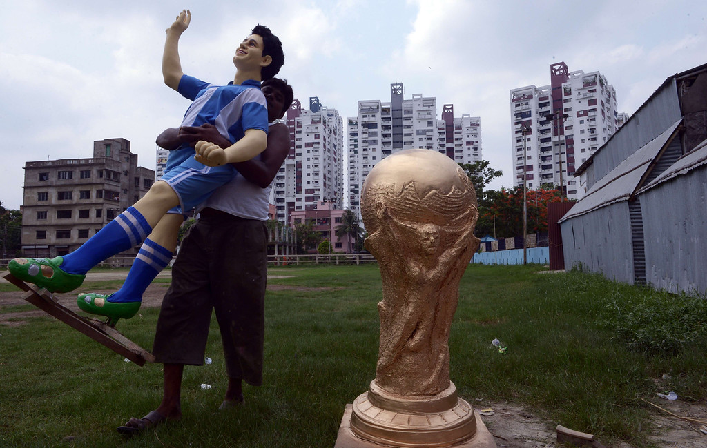 . An Indian artist carries a clay idol of Argentine soccer player Lionel Messi alongside a replica of the FIFA World Cup for a football club, outside the workshop in Kolkata on June 10, 2014.   Football fans in the eastern Indian city are gearing up for the upcoming Brazil FIFA World Cup 2014 and decorating their clubs with football-related paraphernalia.  AFP PHOTO/ Dibyangshu SARKAR/AFP/Getty Images