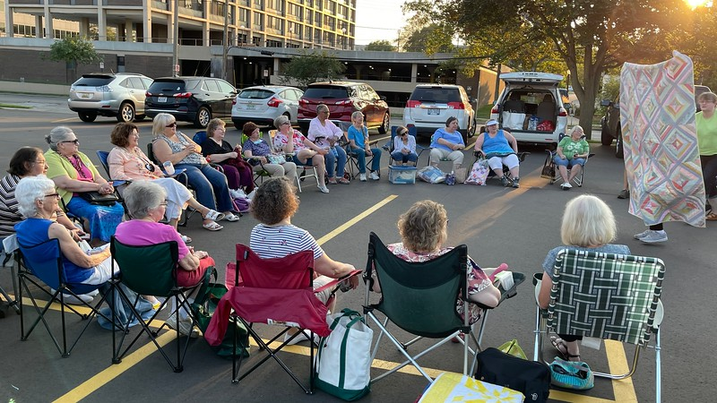 Circle of quilting friends.  This is part of the group at the guild parking-lot-meeting.  Good weather and good quilts.