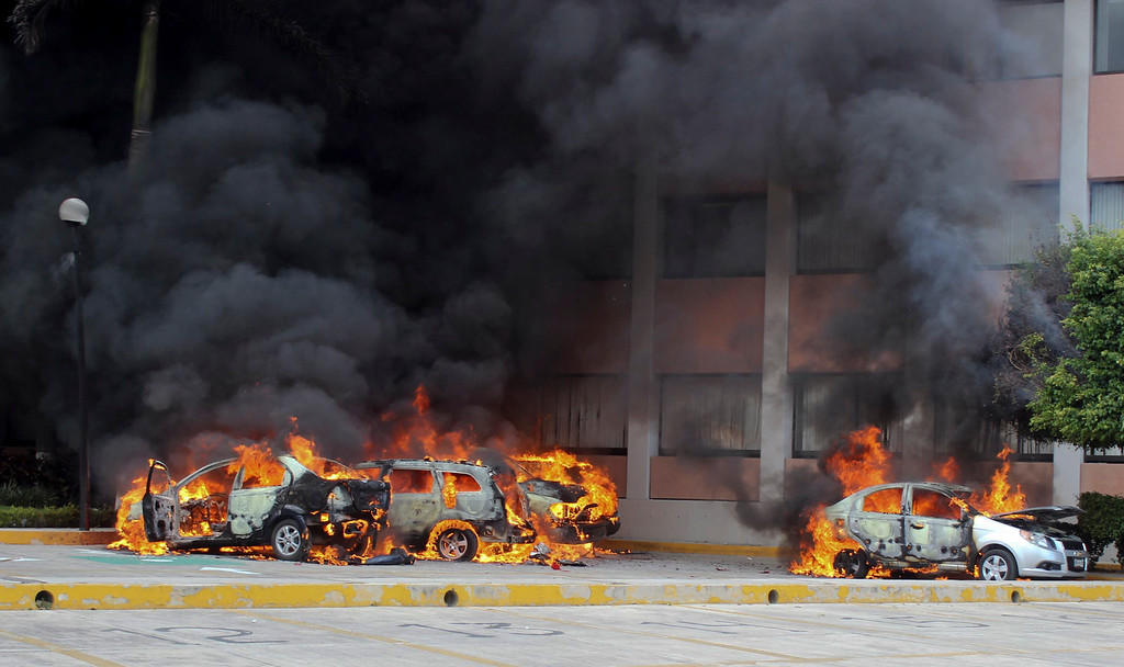 . Cars burn in front of the state congress building after protesting teachers torched them in the state capital city of Chilpancingo, Mexico, Wednesday Nov. 12, 2014. (AP Photo/Alejandrino Gonzalez)