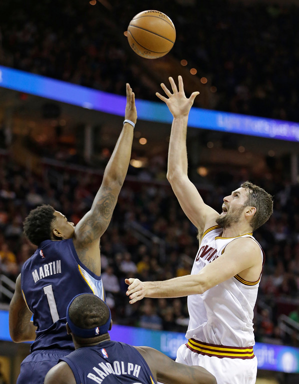 . Cleveland Cavaliers\' Kevin Love (0) shots over Memphis Grizzlies\' Jarell Martin (1) in the first half of an NBA basketball game Tuesday, Dec. 13, 2016, in Cleveland. The Cavaliers won 103-86. (AP Photo/Tony Dejak)