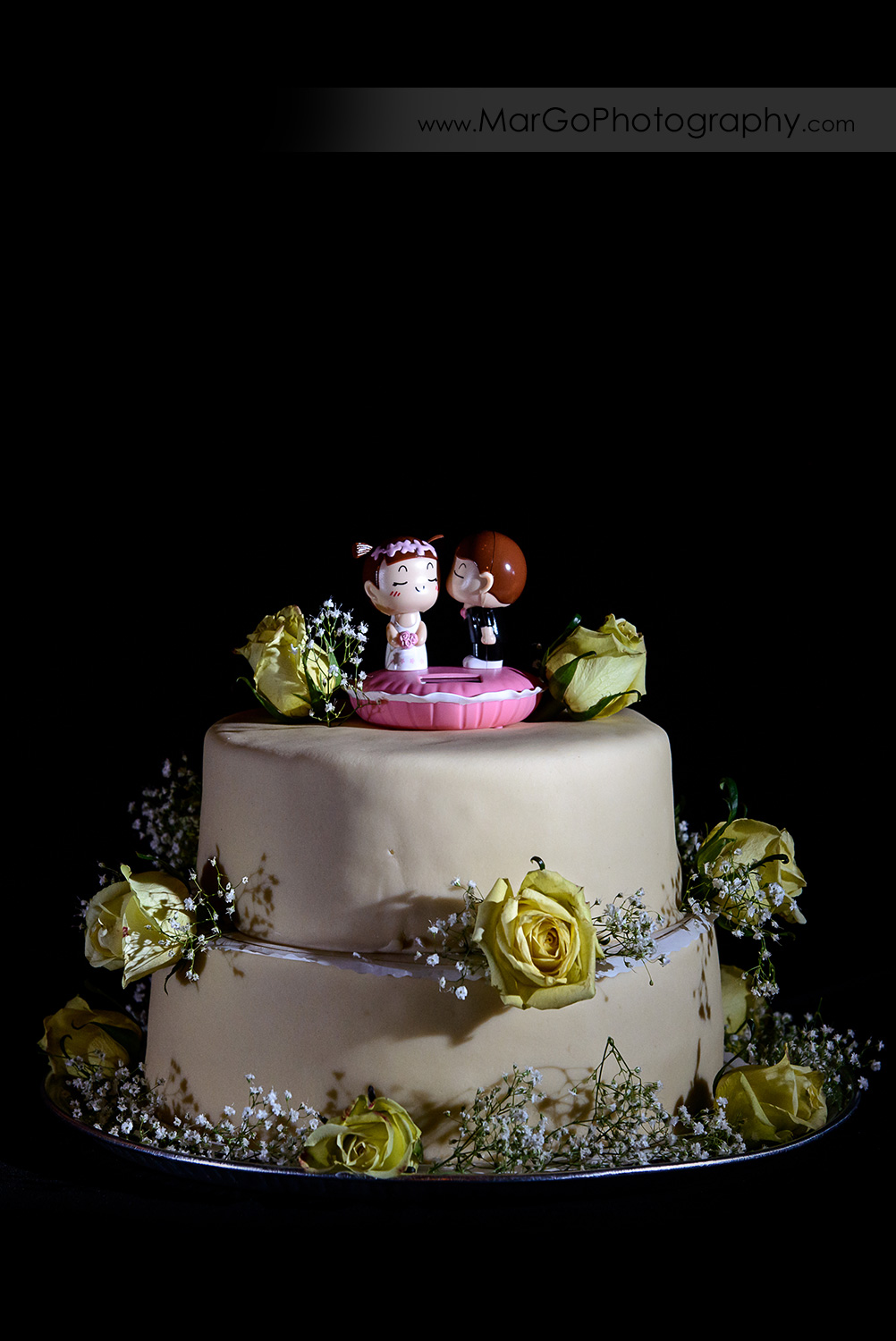 wedding cake decorated with yellow roses and manga topper