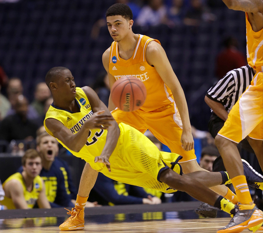. Michigan\'s Caris LeVert falls as he tries to pass around Tennessee\'s Darius Thompson during the second half of an NCAA Midwest Regional semifinal college basketball tournament game Friday, March 28, 2014, in Indianapolis. (AP Photo/David J. Phillip)