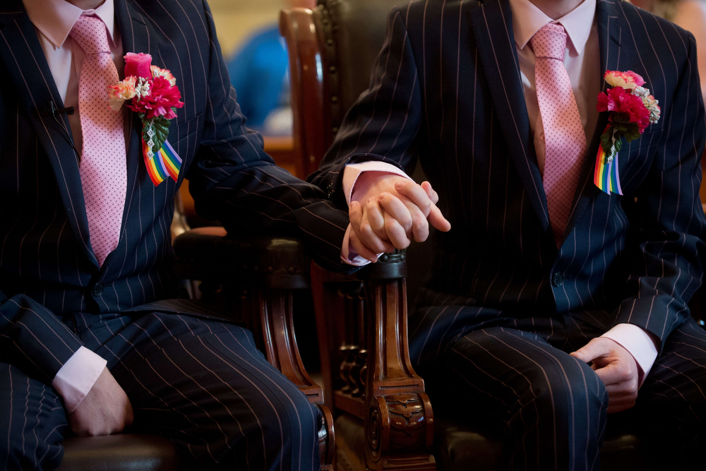 """. Phil Robathan (L) and James Preston (R) hold hands during their wedding ceremony in Brighton, southern England, on March 29, 2014. Gay couples across England and Wales said \""""I do\"""" as a law legalizing same-sex marriage came into effect at midnight, the final stage in a long fight for equality.  (LEON NEAL/AFP/Getty Images)"""
