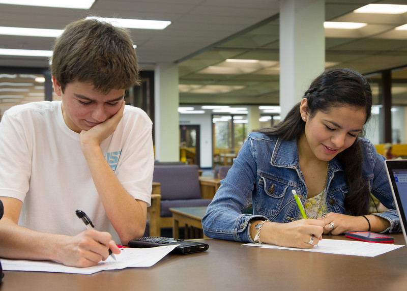 Students Reed Miller(left) and Kimberly Jacinto help each other with Calculus I work.