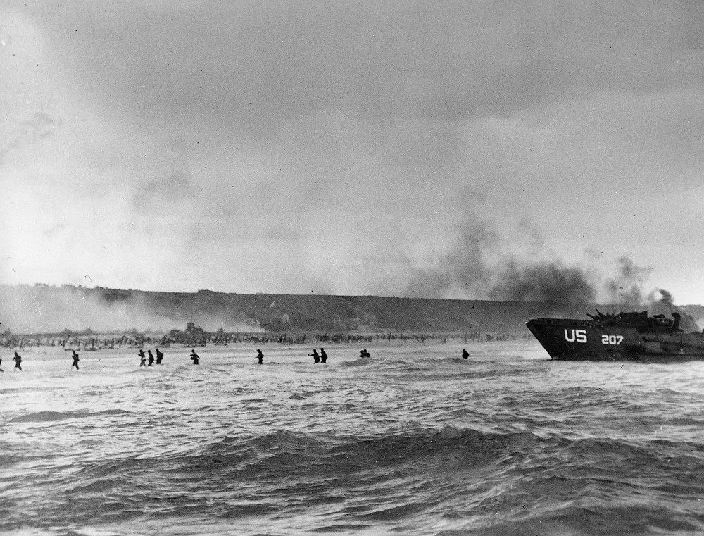 Description of . Under the cover of naval shell fire, American infantrymen wade ashore from their landing craft during the initial Normandy landing operations in France, June 6, 1944. (AP Photo/Peter Carroll)