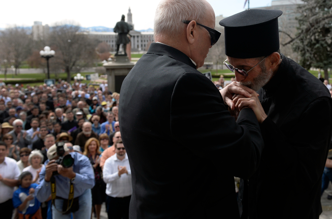 . Fr. Ambrose Omayas, right, from the Greek Orthodox Metropolis Cathedral of Denver, kisses the hand of the Catholic Archbishop of Denver Samuel J. Aquila after the two finish praying and speaking about their opposition to Senate Bill 175 to a crowd gathered on the west steps of the state Capitol in Denver on April 15, 2014. The bill would prohibit a state or local policy that denies or interferes with an individual\'s reproductive health care decisions. (Kathryn Scott Osler, The Denver Post)