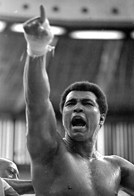 """. World heavyweight champion Muhammad Ali shouts \""""Joe Bugner must go!\"""" to Malaysian fans during a training session at a Kuala Lumpur stadium, June 15, 1975. Ali defends his title against Britain\'s European champion Joe Bugner on July 1. (AP Photo)"""