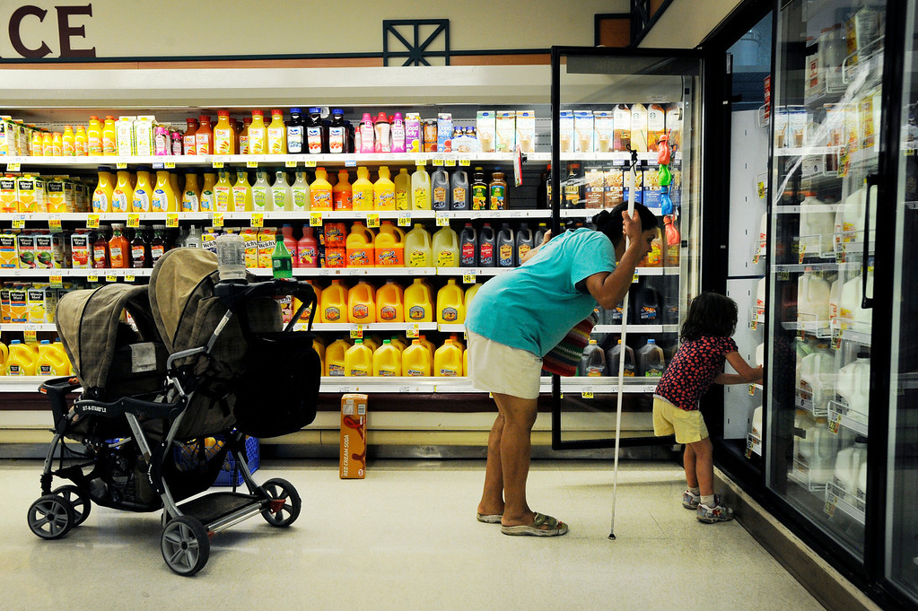 . Olivia, 4, right, helps her mom find the proper milk at a King Soopers in Littleton, Colorado. Ena and Brent Batron are both blind, and raising five kids under the age of 10. June 28, Denver, Colo.  Photo by Jamie Cotten, Special to The Denver Post