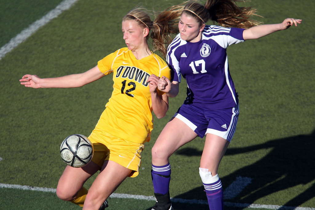. Bishop O\'Dowd\'s Darby Nordin (12) and Piedmont\'s Erin Greening (17) fight for a ball in the first half of overtime of their North Coast Section Division II Girls Soccer Championship at Dublin High School soccer field in Dublin, Calif., on Saturday, Feb. 23, 2013. Bishop O\'Dowd won 3-2 in a series of penalty kicks. (Ray Chavez/Staff)