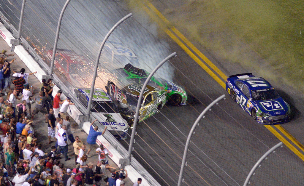 . Danica Patrick (10), David Gilliland (38), Ricky Stenhouse Jr. (17), Kyle Busch (18), J J Yeley (36) and Casey Mears (13) slide along the wall of the front stretch after colliding on the final lap during the NASCAR Sprint Cup auto race at Daytona International Speedway in Daytona Beach, Fla., Saturday, July 6, 2013. (AP Photo/Phelan M. Ebenhack)