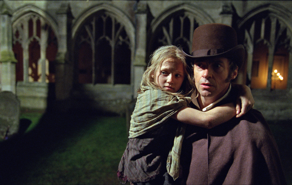 Description of . This publicity film image released by Universal Pictures shows Hugh Jackman as Jean Valjean holding Isabelle Allen as Young Cosette in a scene from