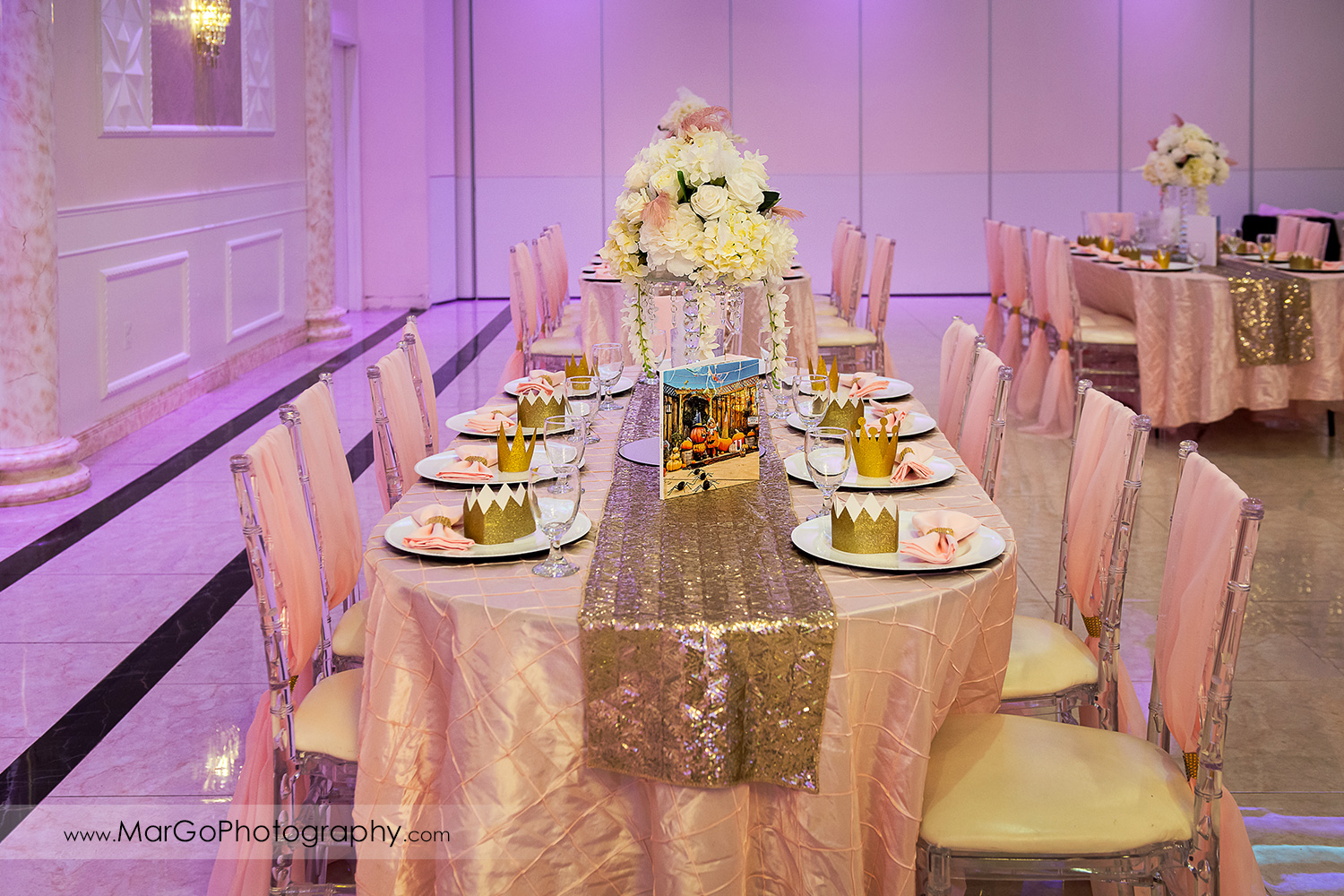 pink and golden table decor with white flower centerpiece at Newark Oasis Palace