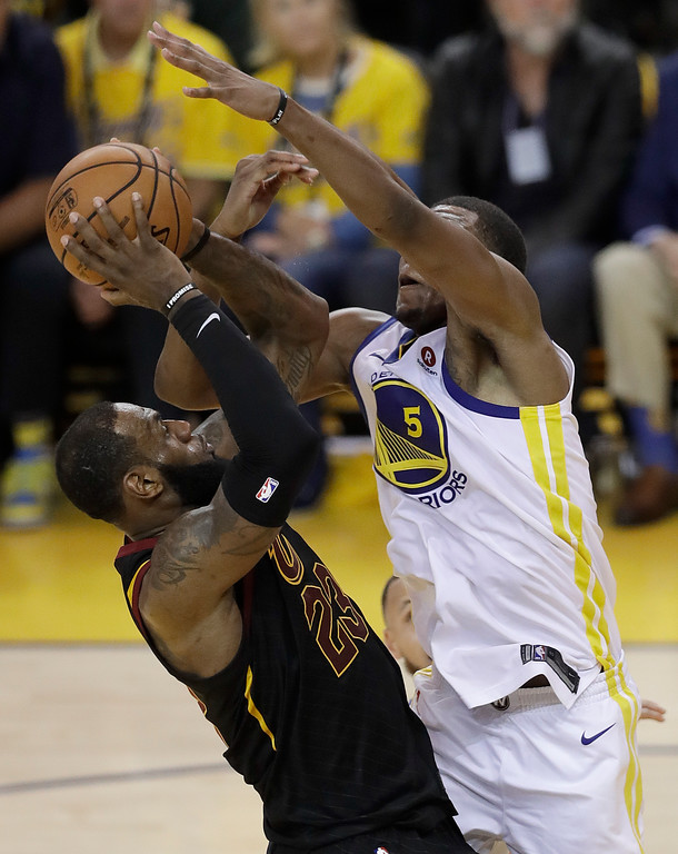 . Cleveland Cavaliers forward LeBron James, left, shoots while defended by Golden State Warriors forward Kevon Looney during the second half of Game 1 of basketball\'s NBA Finals in Oakland, Calif., Thursday, May 31, 2018. (AP Photo/Marcio Jose Sanchez)