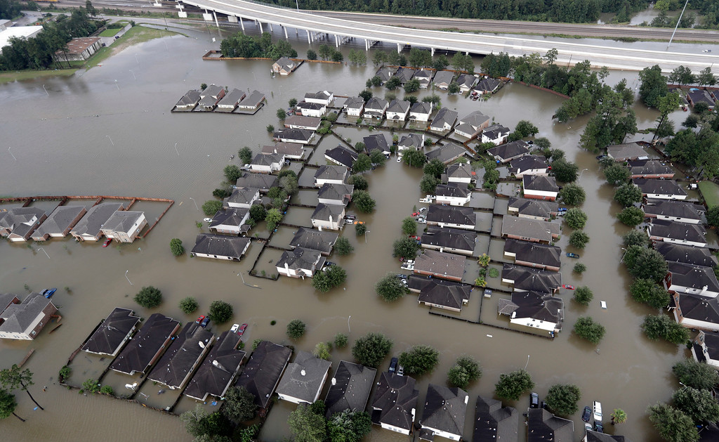 . Homes are surrounded by floodwaters from Tropical Storm Harvey Tuesday, Aug. 29, 2017, in Spring, Texas. (AP Photo/David J. Phillip)