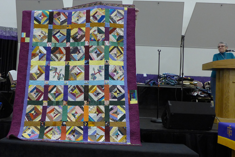 Billie Piazza started making this string quilt using copy paper rather than newsprint.  She has a brother that has not yet received one of her quilts.  The corner blocks have fabrics that have bicycles, flowers, sailboats, seagulls and tool.  He lives on Mackinaw Island.