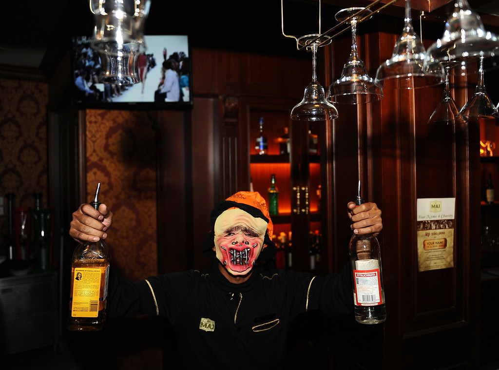 . A bartender works in costume during a Halloween party at Majapahit Hotel on October 31, 2013 in Surabaya, Indonesia.  Revelers across the country are celebrating Halloween the day before the Christian All Saints\' Day, which  honors the dead.  (Photo by Robertus Pudyanto/Getty Images)