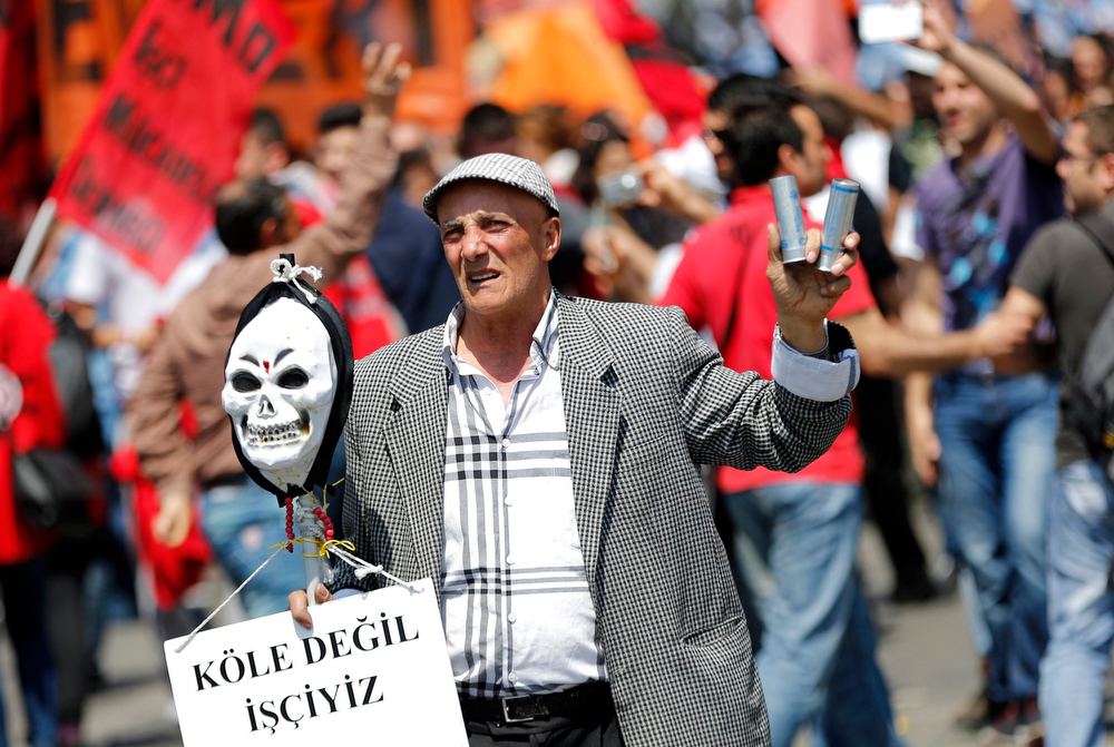 . A May Day protester holds a placard, a mask and tear gas canisters during clashes with riot police in central Istanbul May 1, 2013. Turkish riot police clashed with thousands of May Day protesters in Istanbul on Wednesday, firing water cannon and tear gas at crowds that tried to break through barricades to reach the city\'s main square, witnesses said. The incidents followed the pattern of recent years, when May Day demonstrations in Turkey\'s largest city have often been marked by clashes between police and protesters. The placard reads, \'\'We are not slaves, we are workers\'\'.   REUTERS/Murad Sezer