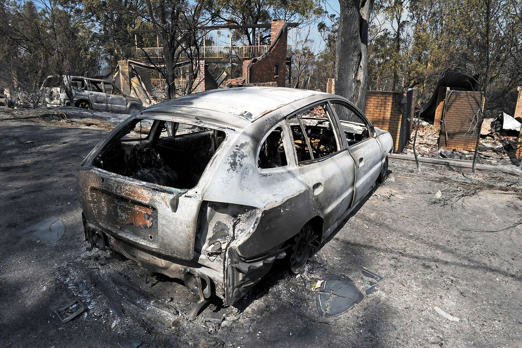 . A burnt out car sits in front of a house destroyed by bush fires in Winmalee in Sydney\'s Blue Mountains on October 18, 2013.  AFP PHOTO / Greg WOOD/AFP/Getty Images