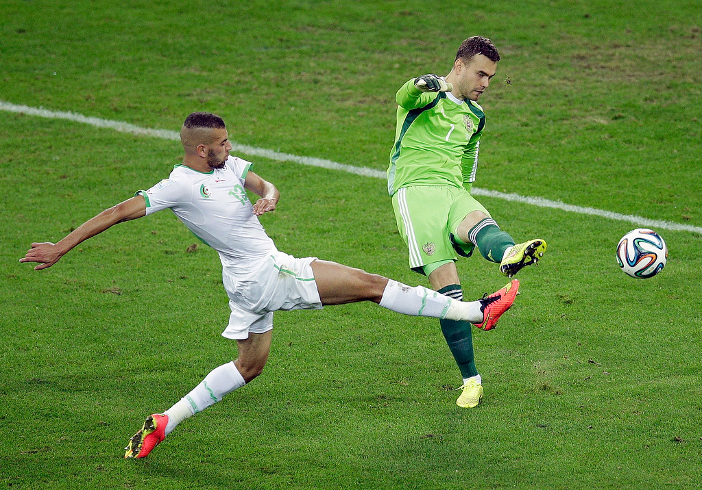 . Algeria\'s Islam Slimani, left, challenges Russia\'s goalkeeper Igor Akinfeev for the ball during the group H World Cup soccer match between Algeria and Russia at the Arena da Baixada in Curitiba, Brazil, Thursday, June 26, 2014. (AP Photo/Michael Sohn)