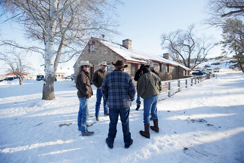 . Ammon Bundy, center, one of the sons of Nevada rancher Cliven Bundy, huddles with a group of man at Malheur National Wildlife Refuge Friday, Jan. 8, 2016, near Burns, Ore. Bundy, the leader of a small, armed group occupying a national wildlife refuge in Oregon says the activists have no immediate plans to leave. Bundy spoke to reporters Friday, a day after meeting with a local sheriff who asked the group to go. (AP Photo/Rick Bowmer)