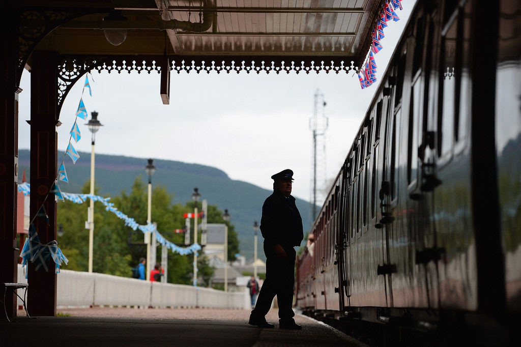 . Guard Brian Burgess waves off the 1952 British Rail Ivatt number 46512 at Strathspey Steam Railway on August 27, 2013 in Aviemore, Scotland.   (Photo by Jeff J Mitchell/Getty Images)