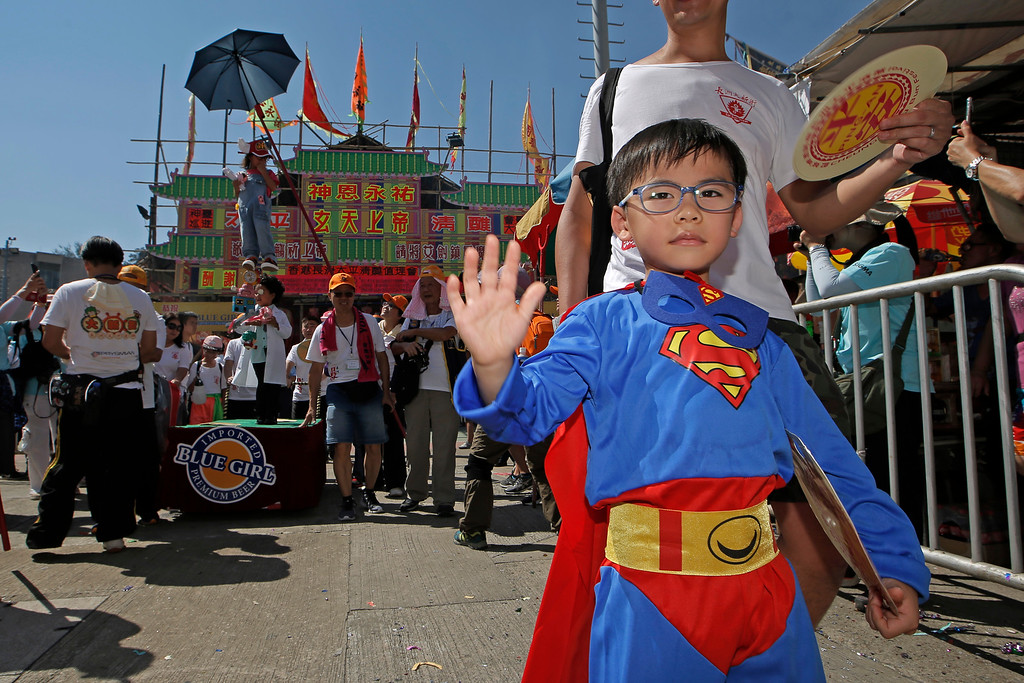 . A child dressed in superman costume joins a parade on the outlying Cheung Chau island in Hong Kong to celebrate the Bun Festival Tuesday, May 22, 2018. Bun Festival, the Taoist God of the Sea, is worshipped and evil spirits are scared away by loud gongs and drums during the procession. The celebration includes bun scrambling, parades, opera performances, and children dressed in colorful costumes. (AP Photo/Kin Cheung)