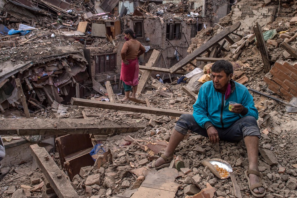 . Nepalese earthquake victims take a break as they search for their belongings among debris of their home on April 29, 2015 in Bhaktapur, Nepal. A major 7.8 earthquake hit Kathmandu mid-day on Saturday, and was followed by multiple aftershocks that triggered avalanches on Mt. Everest that buried mountain climbers in their base camps. Many houses, buildings and temples in the capital were destroyed during the earthquake, leaving over 5000 dead and many more trapped under the debris, as emergency rescue workers attempt to clear debris and find survivors. Regular aftershocks have hampered recovery missions as locals, officials and aid workers attempt to recover bodies from the rubble.  (Photo by David Ramos/Getty Images)