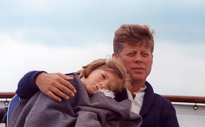 Description of . President John F. Kennedy sits with daughter Caroline aboard the