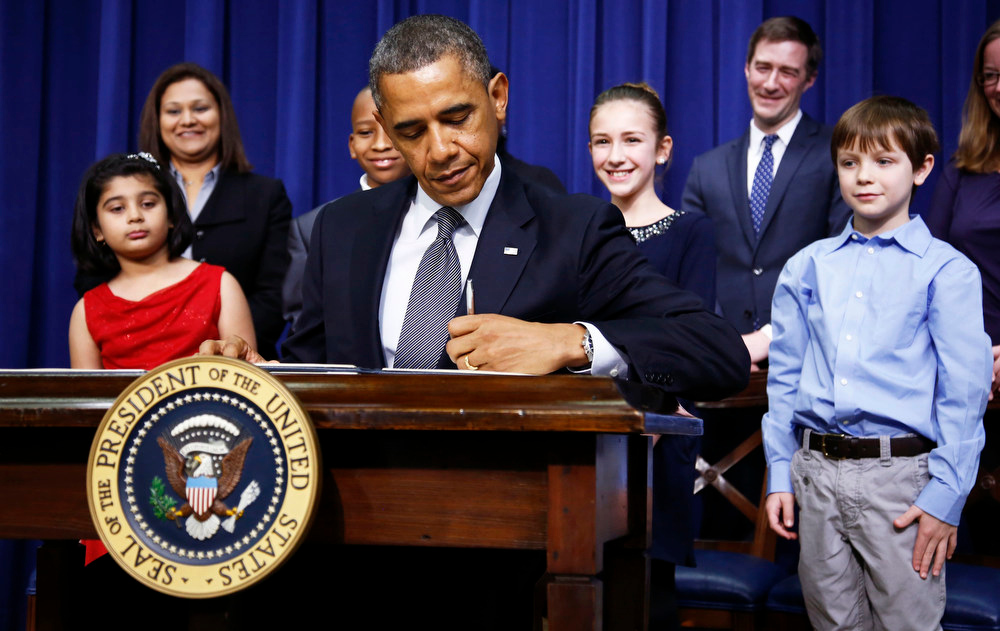 . President Barack Obama signs executive orders on gun violence flanked by 8-year old letter writer Hinna Zeejah (L), 10-year old letter writer Taejah Goode (3rd L), 11-year old letter writer Julia Stokes and 8-year old letter writer Grant Fritz (R) during an event at the White House in Washington, January 16, 2013. Behind the children are Hinna\'s mother Nadia Zeejah (L) and Julia\'s Dad Dr. Theophil Stokes (2nd R). Vice President Joe Biden delivered his recommendations to Obama after holding a series of meetings with representatives from the weapons and entertainment industries as requested by the president after the December 14 school shooting in Newtown, Connecticut, in which 20 children and six adults were killed. REUTERS/Jason Reed