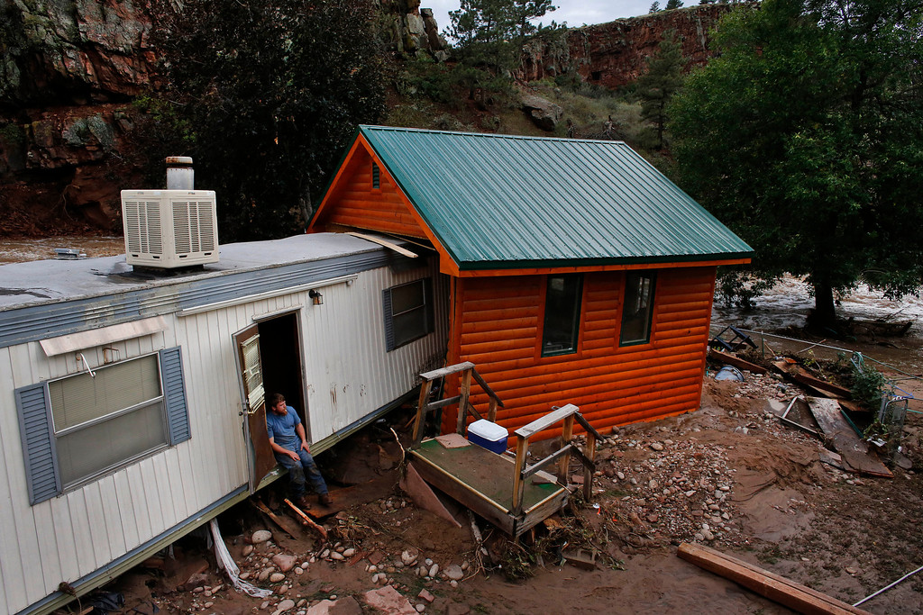 . Local resident Fred Rob sits in the doorway of his home, destroyed by floods which left his town in a shambles , in Lyons, Colo., Friday Sept. 13, 2013. Days of heavy rains and flash floods which washed out the town\'s bridges and destroyed the electrical and sanitation infrastructure have left many Lyons residents stranded with minimal access to help, and sectioned off the town into several pieces not reachable one to the other. (AP Photo/Brennan Linsley)