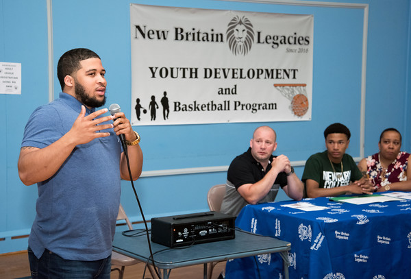 05/25/18 Wesley Bunnell | Staff Coach for Academic Family Basketball Freedom Phil Smith-Beltran who has coached Francisco Santiago II speaks to the attendees before Santiago signed his papersto attend and play basketball for Newbury College. Parents Francisco Santiago Sr and Marsha Michaud sit on either side of him.