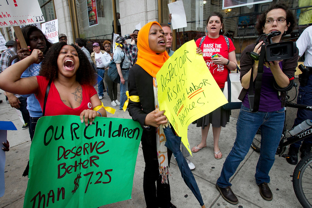 . Fast food workers Danielle Wilson, left, and Justice Wallace march with about 100 other protesters demanding a wage increase during a demonstration in front of a McDonalds restaurant in North Philadelphia on Thursday morning May 15, 2014.  (AP Photo/Philadelphia Daily News, Alejandro A. Alvarez)