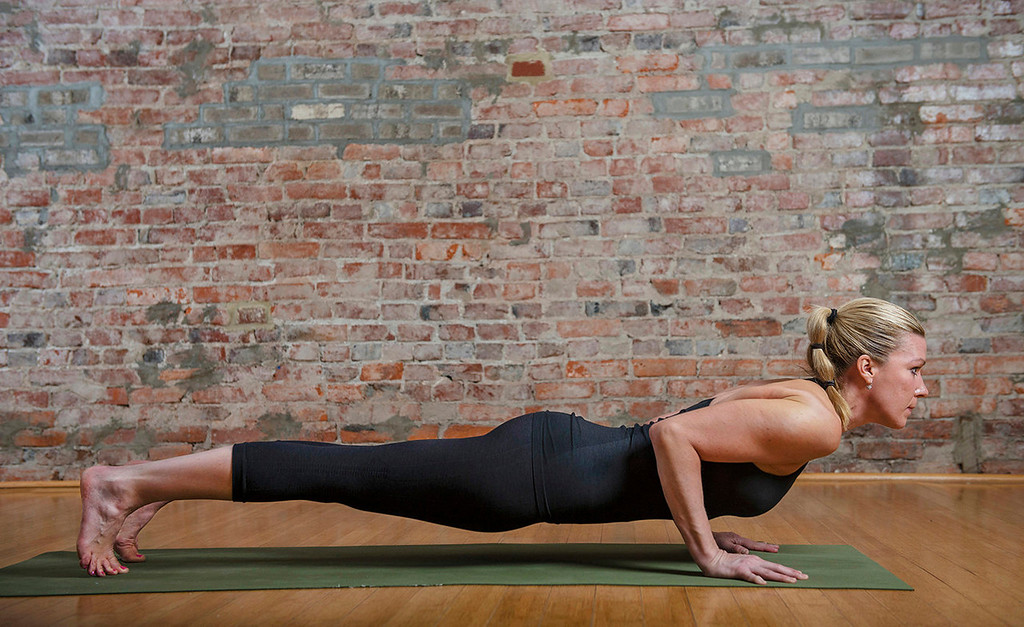 . Sun salutation, left to right:  6) Continuing to exhale, lower yourself until your body is just barely off the ground into chaturanga pose.  (Photo for The Washington Post by Amanda Voisard.)