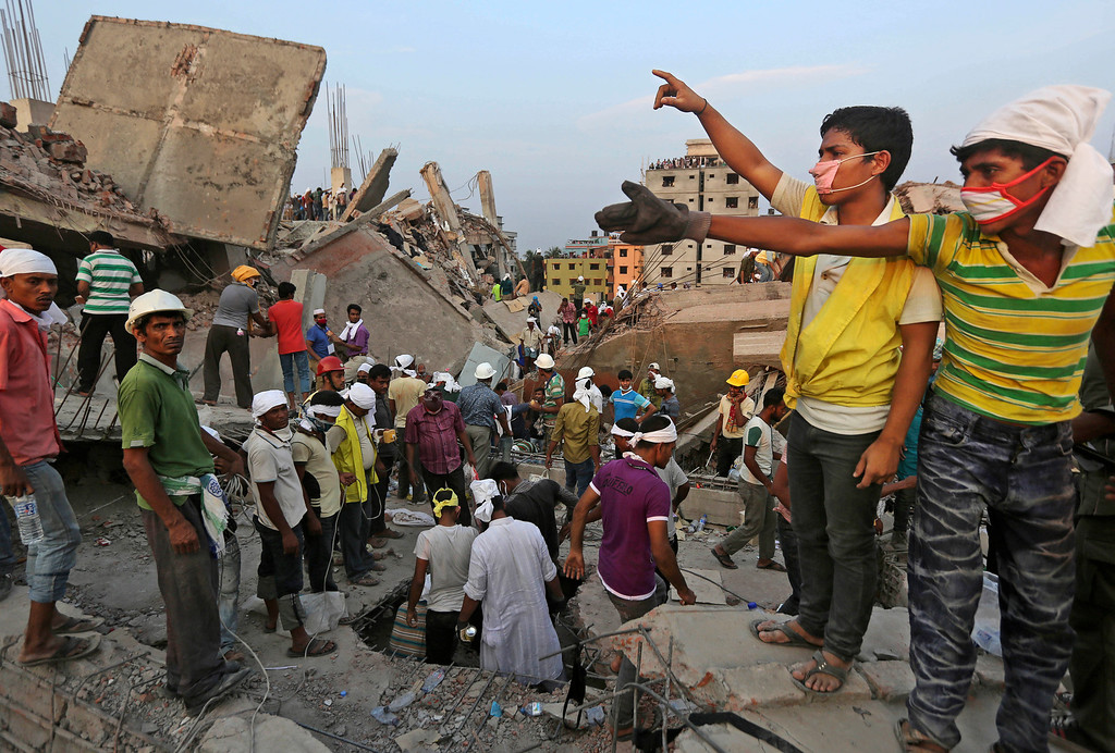 . Bangladeshi rescuers from a youth group gesture for help at the site of a building that collapsed Wednesday in Savar, near Dhaka, Bangladesh, Thursday, April 25, 2013. (AP Photo/Kevin Frayer)