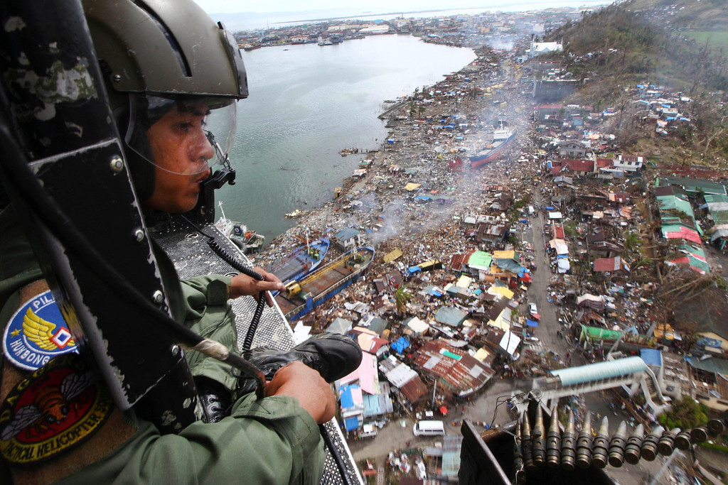 . A Philippine Air Force crew looks out from his helicopter as Typhoon Haiyan-ravaged city of Tacloban is seen in the background, during a flight to deliver relief goods in Leyte province, Philippines, Tuesday, Nov. 19, 2013. Hundreds of thousands of people were displaced by Typhoon Haiyan, which tore across several islands in the eastern Philippines on Nov. 8. (AP Photo/Dita Alangkara)