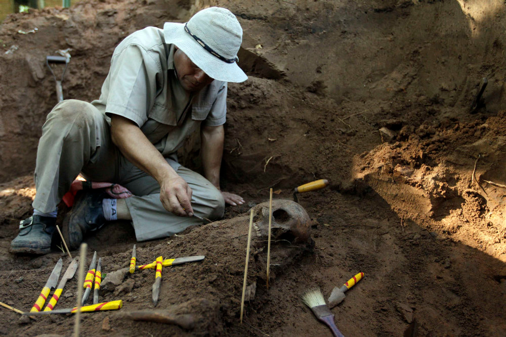 Description of . A member of the police assists in excavating human remains discovered in the grounds of a police barracks in Asuncion, Paraguay on March 21, 2013. According to the researchers, 15 more skeleton remains, likely to be victims of the 1954 to 1989 dictatorship under Alfredo Stroessner, were found in the last two days. REUTERS/Jorge Adorno