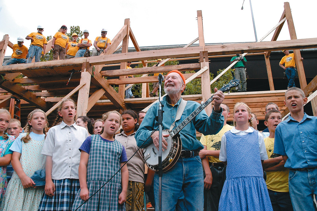 ". Set against the backdrop of the barn with the Timber Framers Guild members and Maritime Museum volunteers standing above, Pete Seeger sings his old standard ""If I Had a Hammer\"" with children from the Bruderhof on  Sept. 15, 2012 on the Roundout in Kingston. Daily Freeman photo by Tania Barricklo."