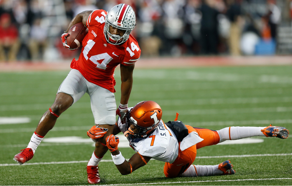 . Ohio State receiver K.J. Hill, left, tries to escape from a tackle by Illinois defensive back Stanley Green during the first half of an NCAA college football game Saturday, Nov. 18, 2017, in Columbus, Ohio. (AP Photo/Jay LaPrete)