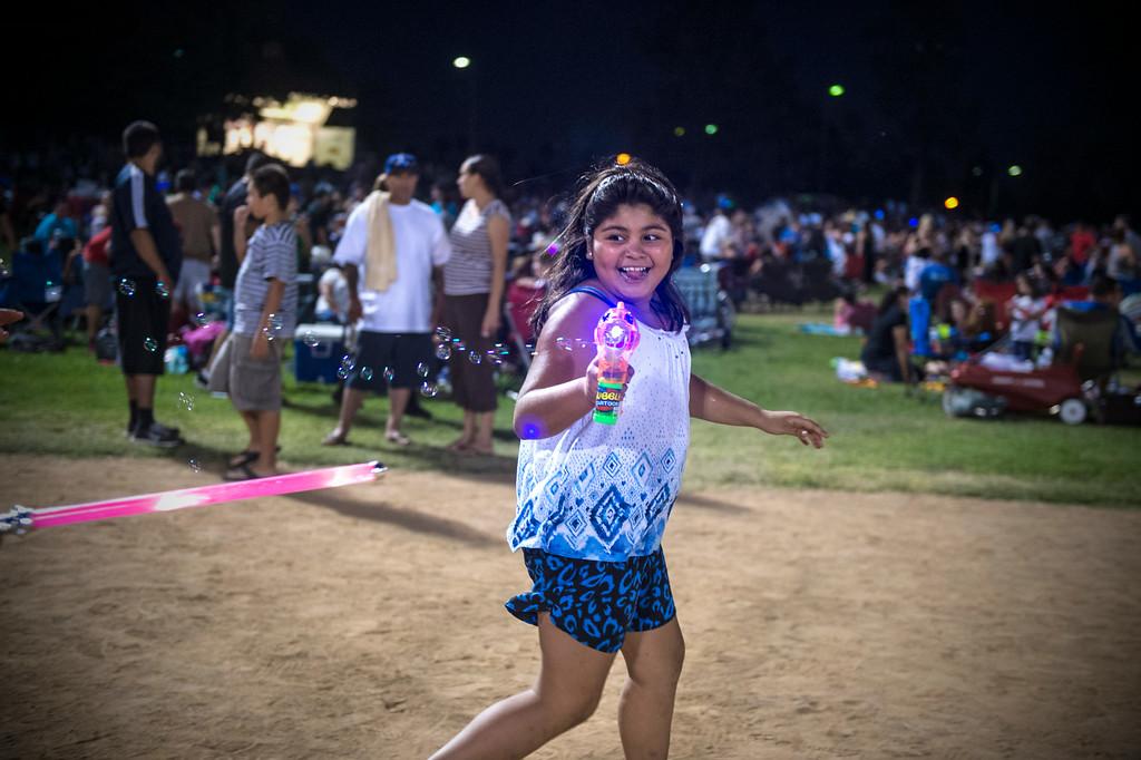 . Isabella Ochoa, 9, of Anaheim, shoots bubbles as she waits for La Mirada\'s annual fireworks show to begin Thursday night, July 3, 2014 at La Mirada Regional Park. (Photo by Sarah Reingewirtz/Pasadena Star-News)
