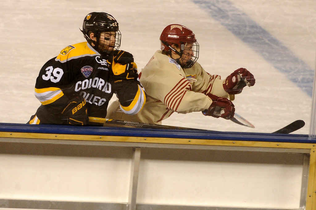 . Andrew Farny (39) of Colorado College avoids the brunt of a check by Emil Romig (18) of the University of Denver during the second period at Coors Field in Denver, Colorado on February 20, 2016. (Photo by Seth McConnell/The Denver Post)
