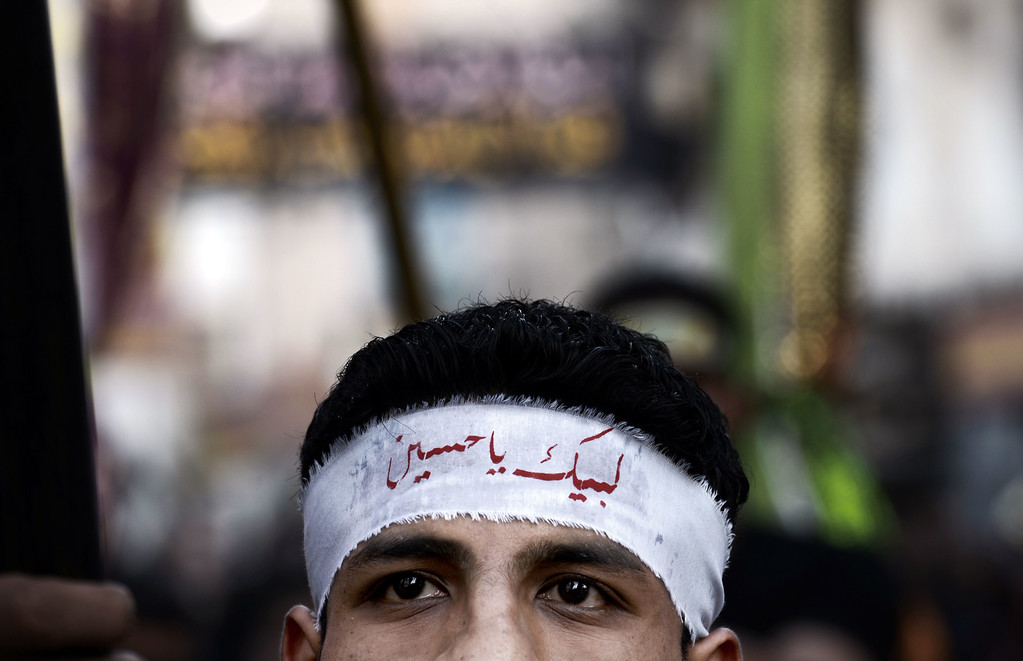 """. A Bahraini Shiite Muslim wearing a headband reading in Arabic \""""Oh Hussein\"""" takes part in a ceremony marking Ashura, which commemorates the seventh century slaying of Imam Hussein, the grandson of Prophet Mohammed, in the village of Sanabis, west of Manama on November 1, 2014. MOHAMMED AL-SHAIKH/AFP/Getty Images"""