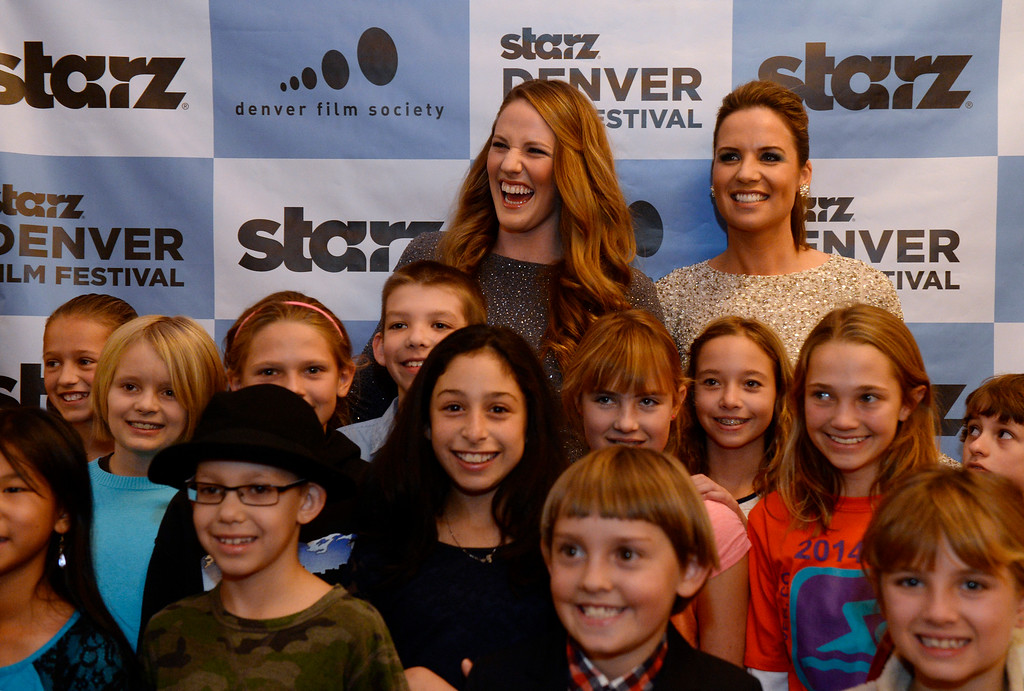 ". Famous Colorado Olympic swimmers Missy Franklin, background left,  and Kara Lynn Joyce, join a red carpet event for the Starz Denver Film Festival with the filmmakers of the documentary made about them titled ""Touch the Wall\"". The two pose for photos with students from Graland Country Day School who helped film a promo for the film festival. The filmmakers, Grant Berbeito and Christo Brock, joined the two women at the festival at the Buell Theatre  in Denver. (Photo by Kathryn Scott Osler/The Denver Post)"