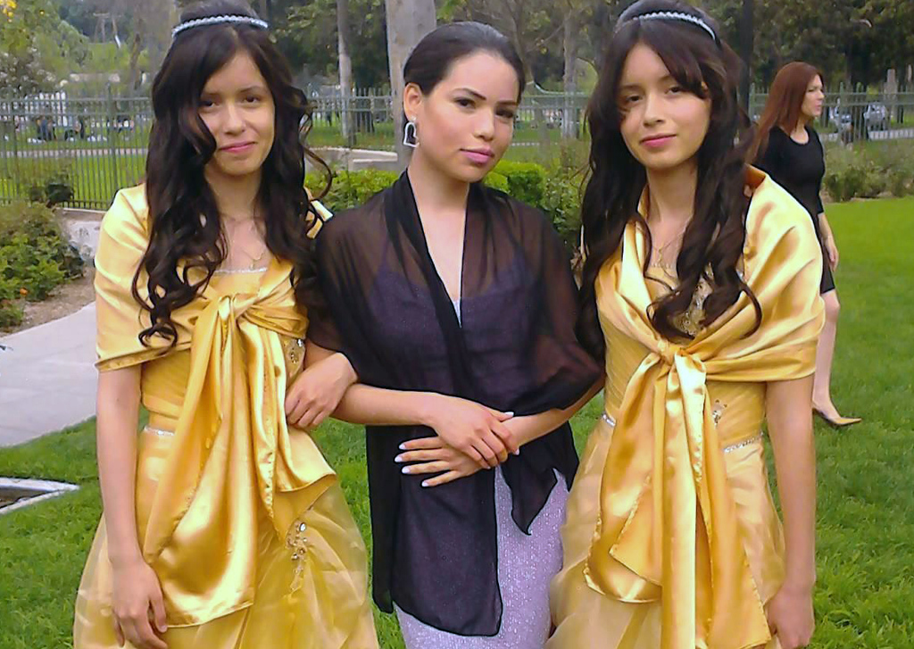 . This 2013 photo provided by Miguel Serrato shows twin sisters Marisol Serrato, 17, left, and Marisa Serrato, right, with their sister-in-law Ivette Serrato during a wedding in Riverside, Caif.  The twins were part of the group more than 40 high school students whose trip to visit a college turned tragic when a FedEx tractor-trailer veered across a grassy highway median and slammed into their bus in a wreck that left 10 people dead, authorities said. Marisa was one of the twins on the bus that crashed but is still unaccounted for. Marisol was on another bus that wasn\'t in the accident. (AP Photo/Courtesy Miguel Serrato)